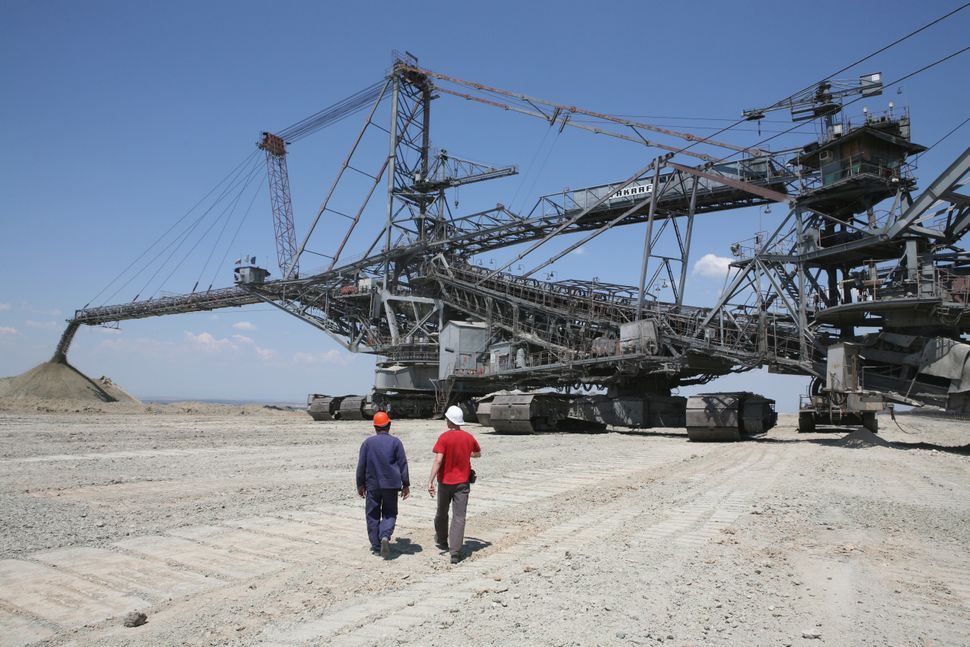 Workers walk toward a huge coal excavator at Maritsa Iztok, the largest coal mine in Bulgaria. Many large excavators, up to 7