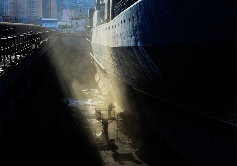 A person works on a large anti-submarine ship docked at the Dalzavod Ship Repair Centre in Vladivostok, Russia, on
