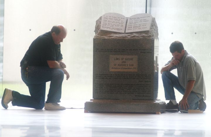 Workers pause before removing a Ten Commandments monument from the rotunda of the state judicial building in M