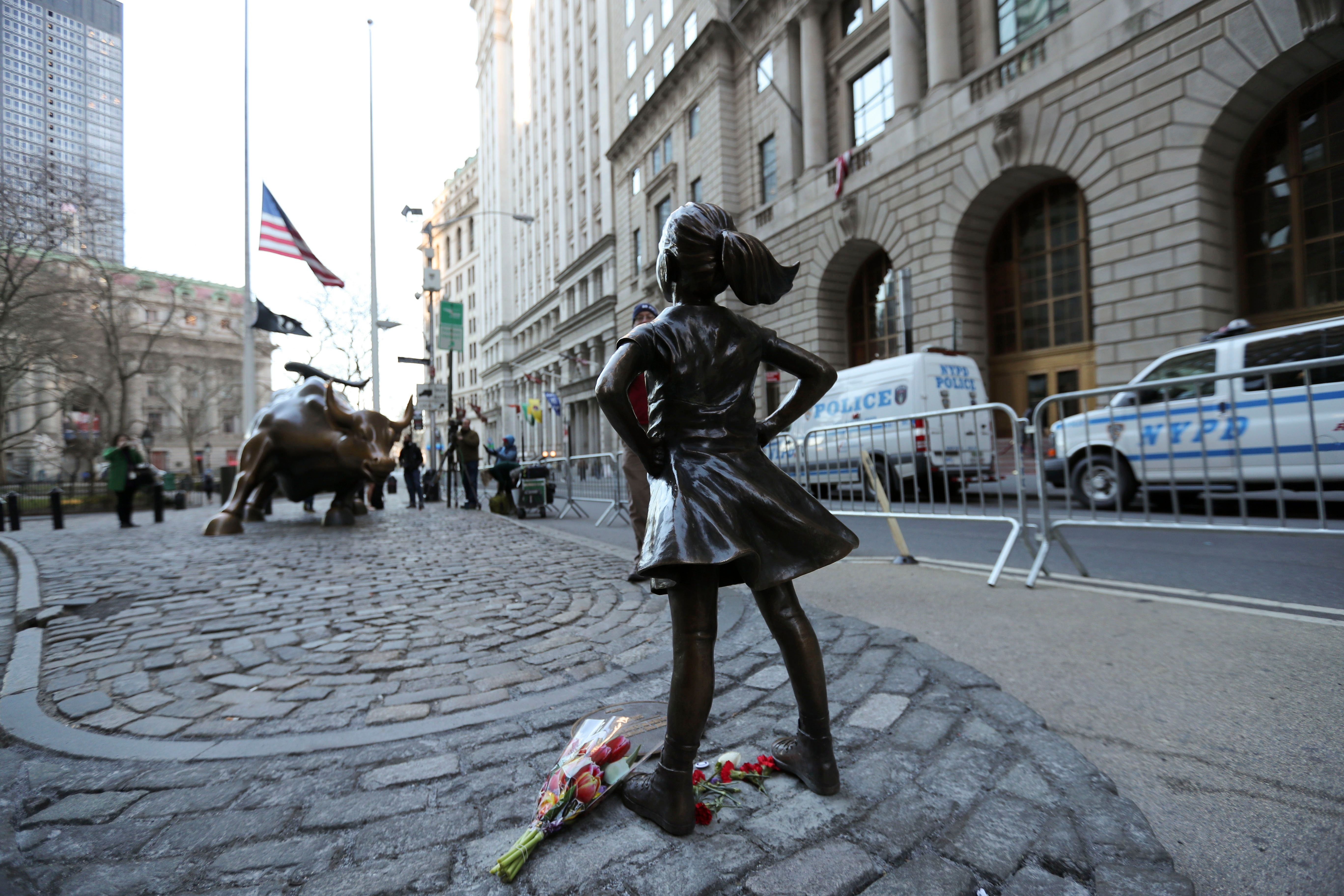 """The """"fearless girl"""" statue faces the bronze bull statue near Wall Street in New York, New York."""