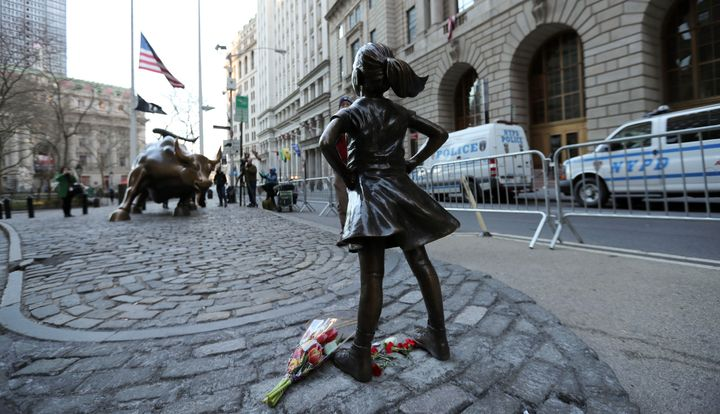 "The ""fearless girl"" statue faces the bronze bull statue near Wall Street in New York, New York."
