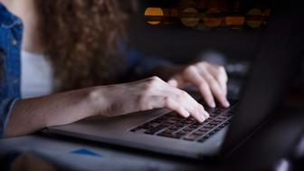 Close up of hands of unrecognizable young woman sitting at desk, working on laptop late at night.