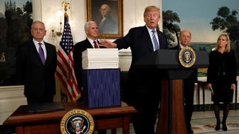 U.S. President Donald Trump gestures towards Congress' $1.3 trillion spending bill, during a signing ceremony, in the Diplomatic Room of the White House in Washington, D.C., U.S., March 23, 2018. REUTERS/Kevin Lamarque