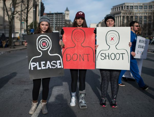 """Demonstrators hold three corresponding signs that read """"PLEASE DON'T SHOOT"""" at the rally inWashington."""