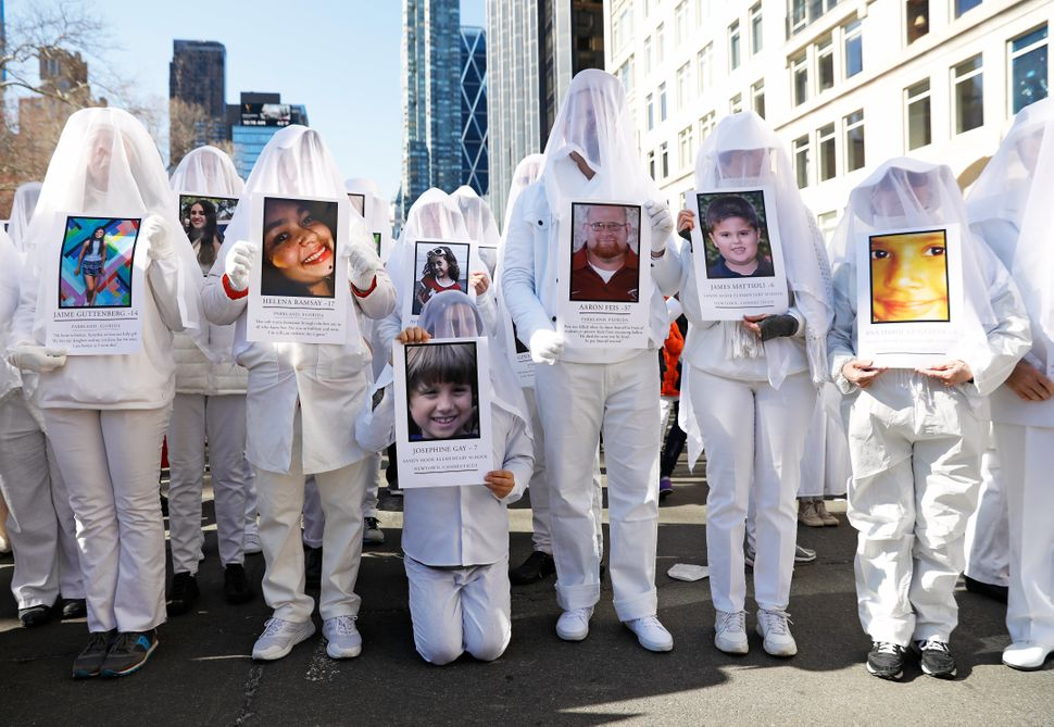 Protesters hold photos of victims of school shootings in New York City.