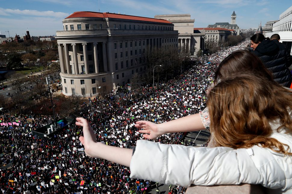 Young girls wave down at marchers from the balcony of the Newseum.