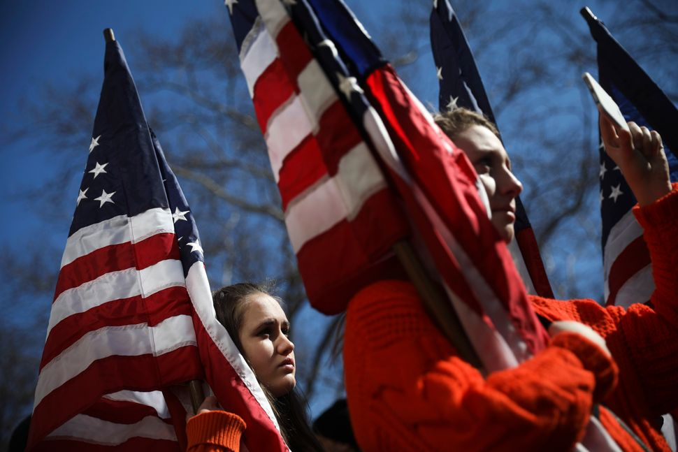 High school students from New Jersey hold American flags as they attend the March For Our Lives just north of Columbus Circle