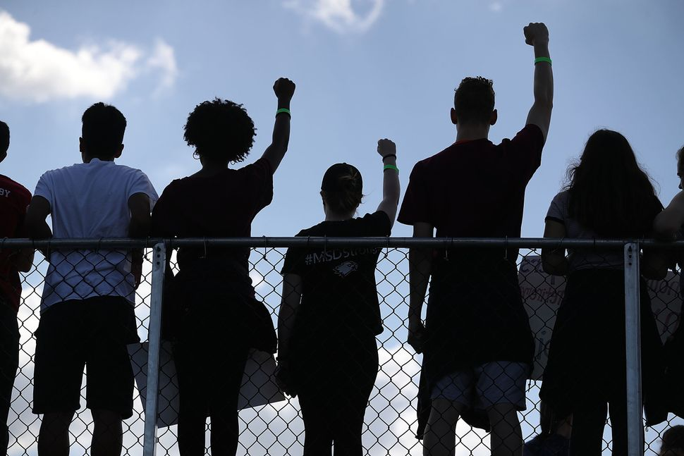 Marjory Stoneman Douglas High School students hold their fists up in the air.
