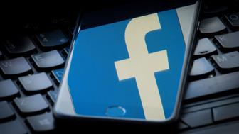 The logo of social networking site Facebook is reflected on the screen of a smartphone resting on a laptop keyboard. (Photo by Dominic Lipinski/PA Images via Getty Images)