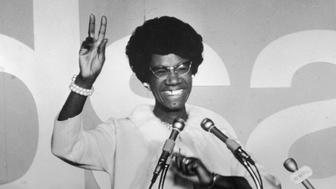 African American educator and U.S. congresswoman Shirley Chisholm stands at a podium and gives the victory sign, circa 1968. (Photo by Pictorial Parade/Getty Images)