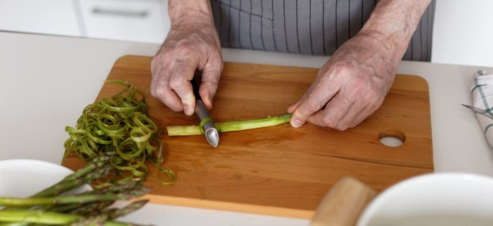 Lay raw asparagus on a cutting board and peel away rough bits with a vegetable peeler.
