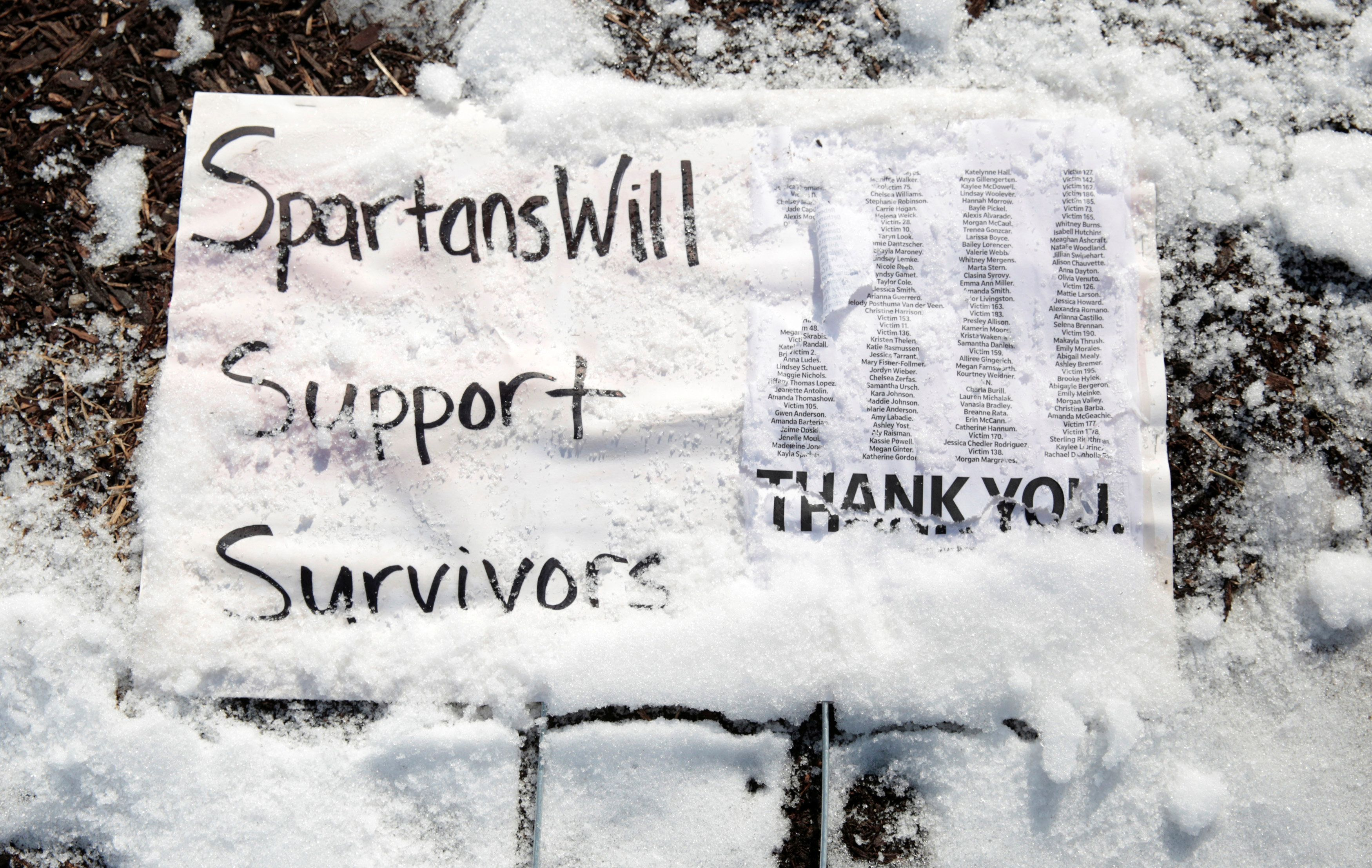 A sign is seen in the snow on the campus of Michigan State University showing support for the assault victims of Larry Nassar, a former team USA Gymnastics doctor who pleaded guilty in November 2017 to sexual assault, in East Lansing, Michigan, U.S., February 1, 2018.   REUTERS/Rebecca Cook