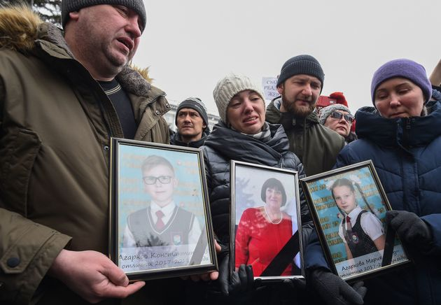 People gather to pay tribute to the victims of a fire at a shopping center in Kemerovo, Russia,...
