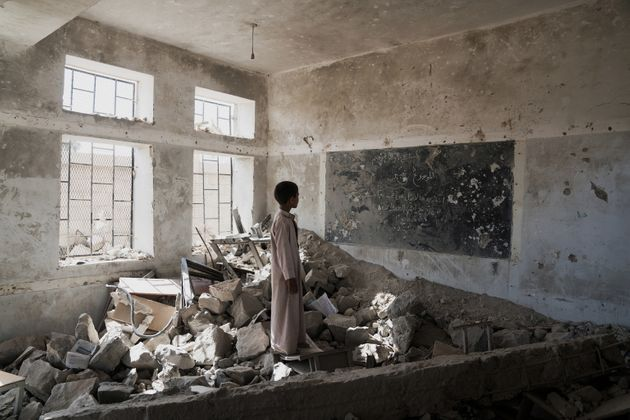 A boy stands in the ruins of his old classroom in Saada,