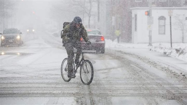A bicyclist crosses the street in Portland, Maine, this month as heavy snow begins to fall. Several states are considering bi