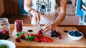 Chinese woman chopping fruit in kitchen