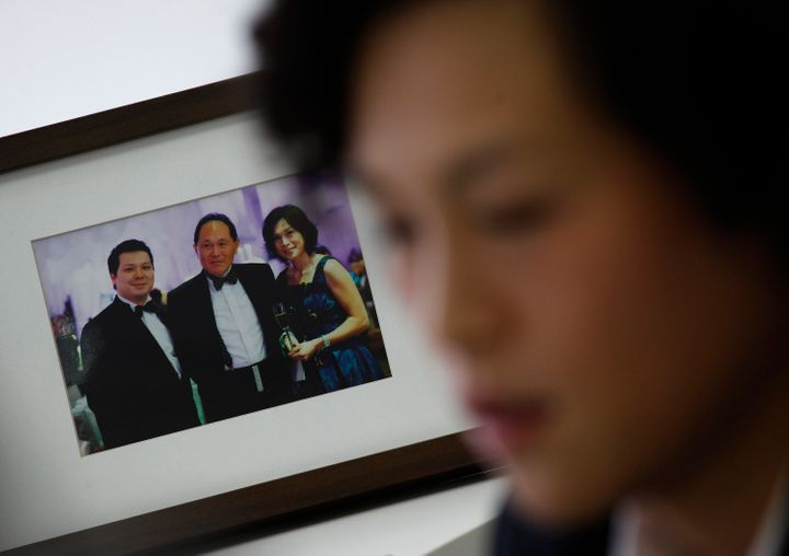 Chao poses next to a family photo of herself, her father (center) and brother Howard.