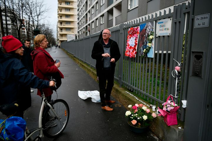 A man places a picture of Mireille Knoll on the fence surrounding her building in Paris on March 27, 2018.