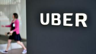 A woman walks into the Uber Corporate Headquarters building in San Francisco, California on February 05, 2018.  The billion-dollar trial pitting Alphabet-owned autonomous driving unit Waymo against Uber started in what could be a blockbuster case between two technology giants over alleged theft of trade secrets. The San Francisco courtroom battle will take place as Waymo and Uber race to perfect self-driving cars that people could summon for rides as desired in a turn away from car ownership.  / AFP PHOTO / JOSH EDELSON        (Photo credit should read JOSH EDELSON/AFP/Getty Images)