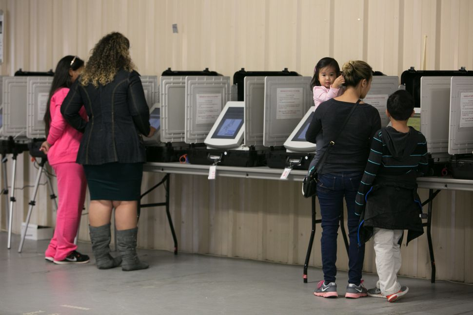 Phonexay Do, right, casts her vote with her children at the Gwinnett County Fairgrounds on Nov. 8, 2016, in Lawrenceville, Ge