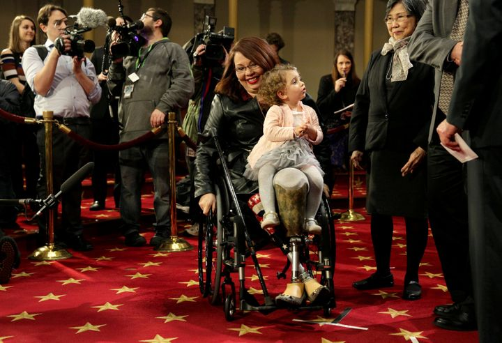 Sen. Tammy Duckworth (D-Ill.) carries her daughter, Abigail, on the opening day of the 115th Congress in January 2017.