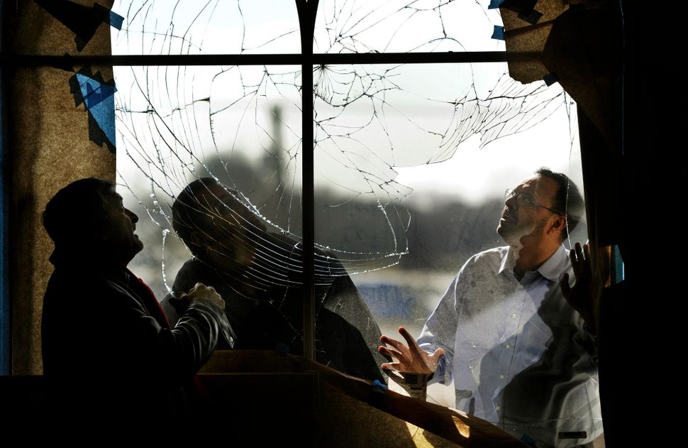 Shahid Malik, Tarek Hasan and Usman Ghumman inspect a vandalized window at the Mubarak Mosque in Chantilly, Virginia, on