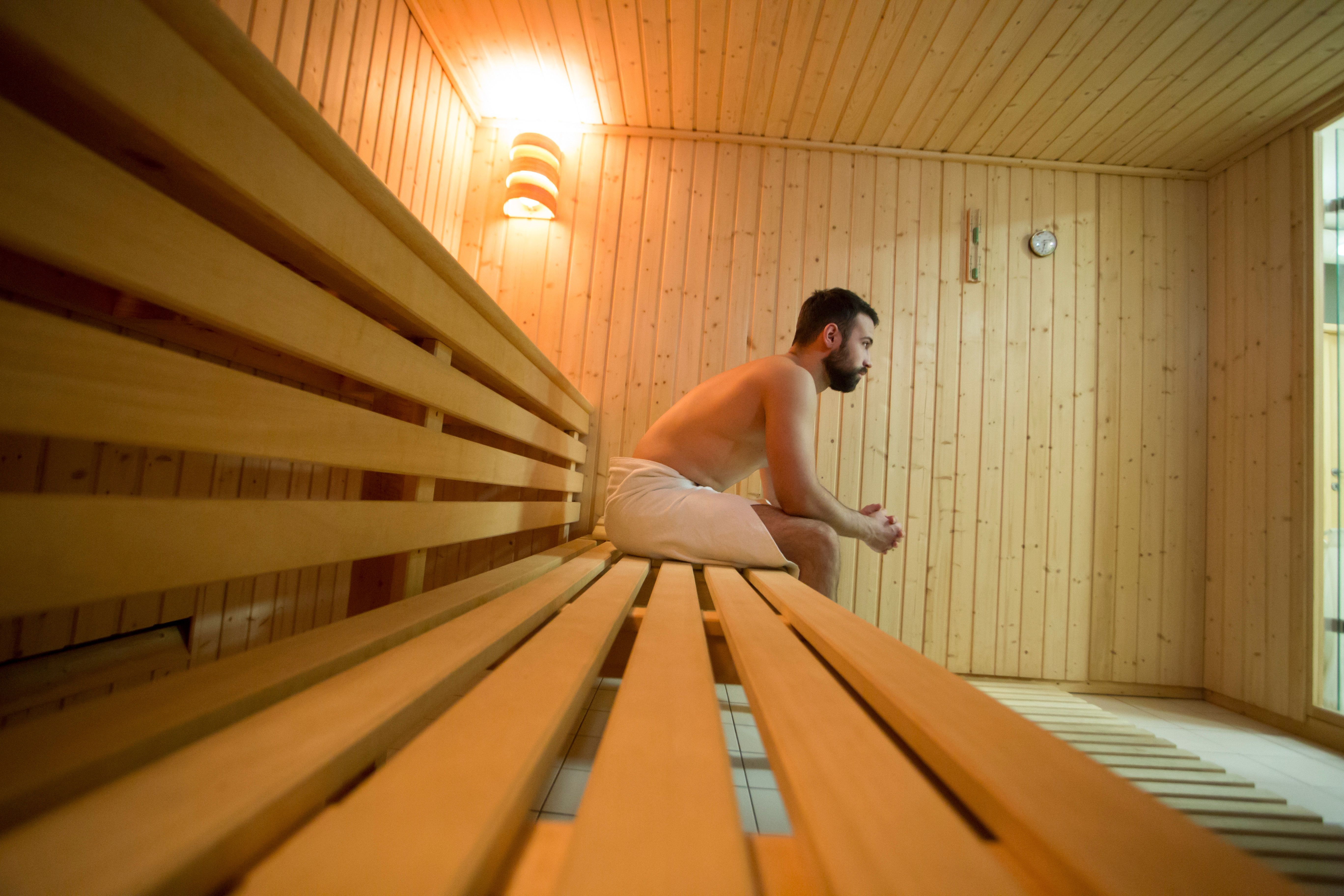 Young man relaxing in a Finnish sauna. About 25 years old, Caucasian male.
