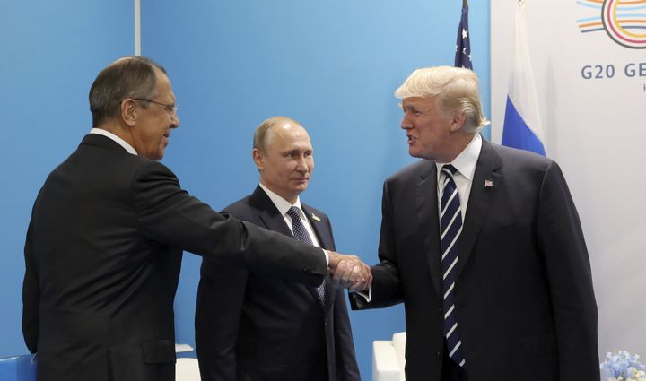 U.S. President Donald Trump shakes hands with Russian Foreign Minister Sergey Lavrov on July 7, 2017, as Russian President Vl