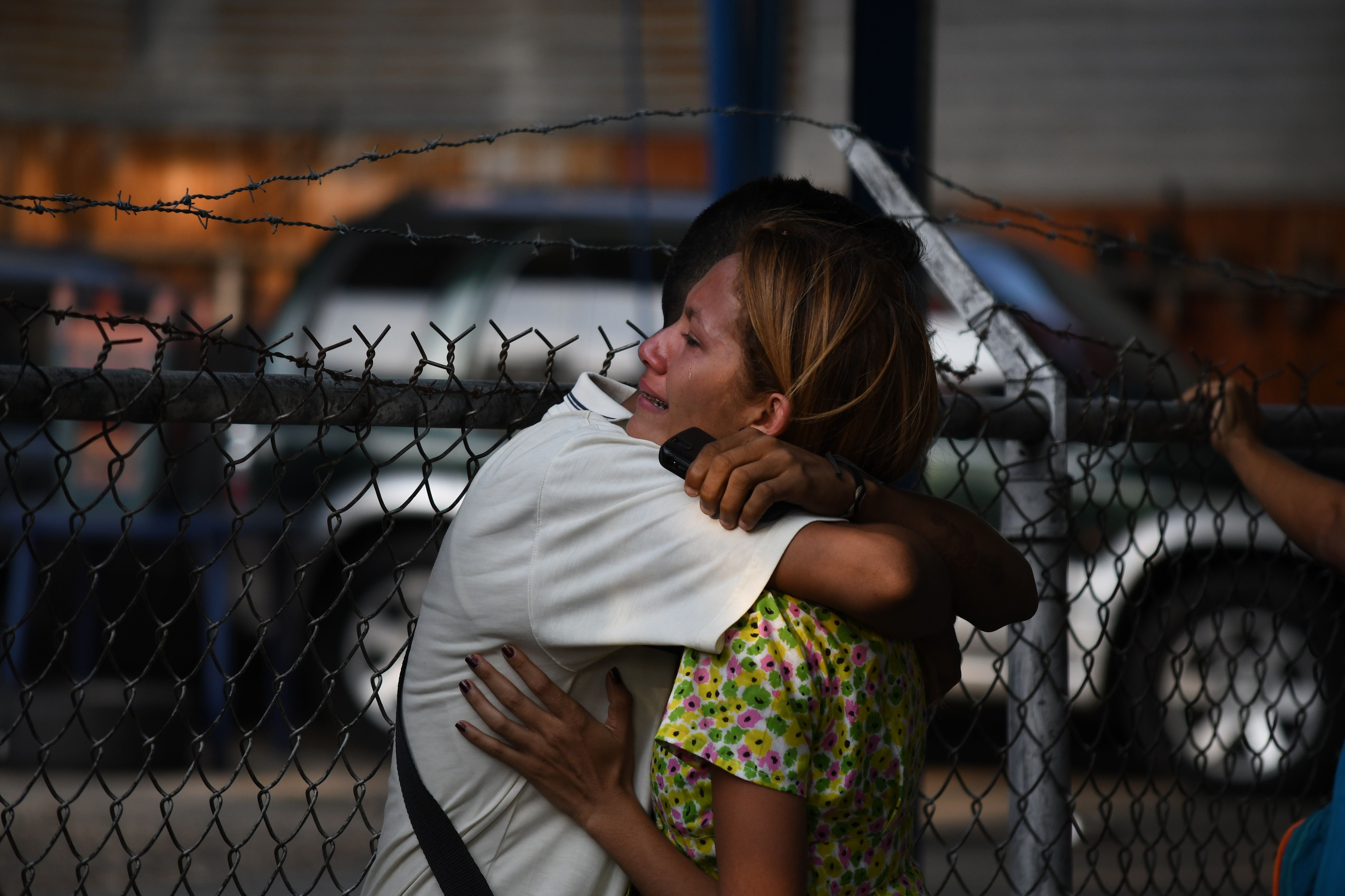 VALENCIA, CARABOBO, VENEZUELA - 2018/03/28: Relatives of detainees seen comforting each other by hugging. Relatives of detainees in the police headquarters of Carabobo, in the city of Valencia in Carabobo state, remain outside the police station waiting to find out if their detained relatives is still alive. A fire inside the cells of the police station taken the lives of 66 detainees and 2 women who were visiting. Family members alleged that the police burned them alive inside the cells after a fight with them. Relatives also reported that police sells weapons inside the prison and charge money for visiting. For more than 20 hours the national government has not release statements and the list of victims. (Photo by Roman Camacho/SOPA Images/LightRocket via Getty Images)