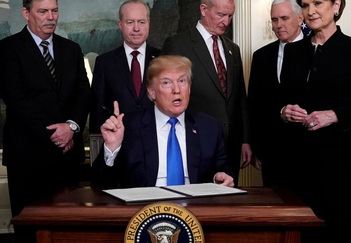 President Donald Trump, surrounded by business leaders and administration officials, prepares to sign a memorandum on intelle
