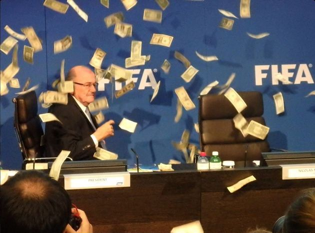 Sepp Blatter surrounded by cash thrown at him by comedian Simon