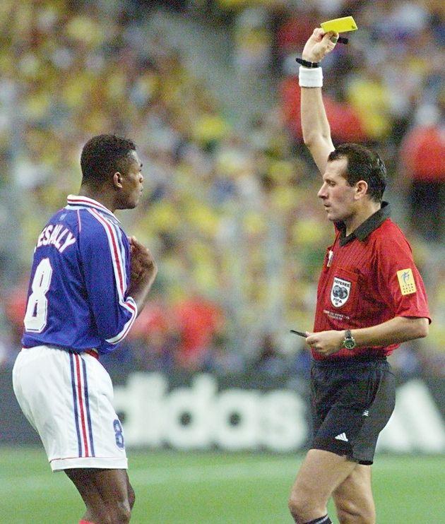 Saïd Belqola lève un carton jaune à l'attention du défenseur Marcel Dessailly,...