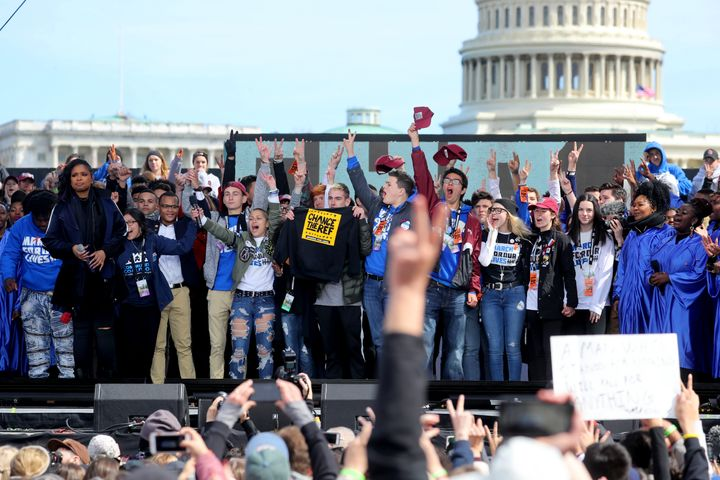 Marjory Stoneman Douglas students wave to the crowd during the March for Our Lives to demand stricter gun control laws on Mar