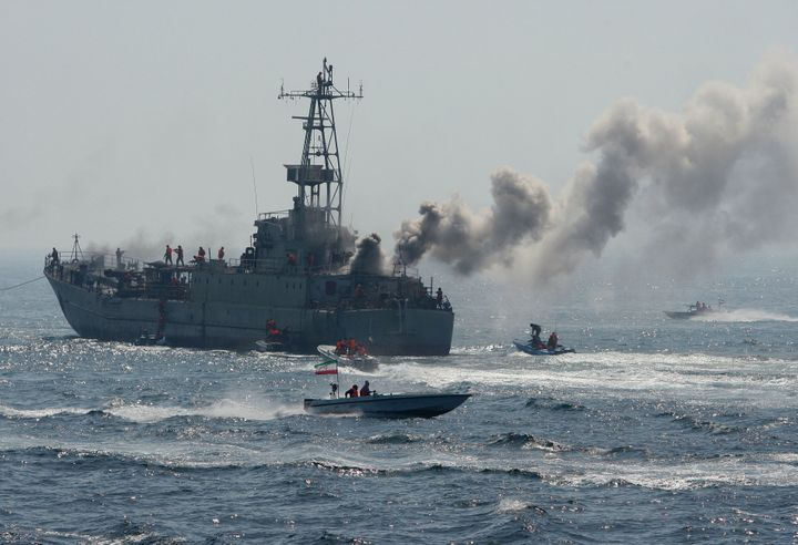 Members of Iran's Revolutionary Guard swarm around a larger naval vessel during military exercises in the Persian G