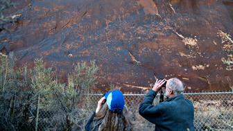 Glo, left, and Ron Auler look at part of the Sand Island Petroglyph Panel was originally part of the Bears Ears National Monument but is no longer in the monument on Wed, March 21, 2018. 