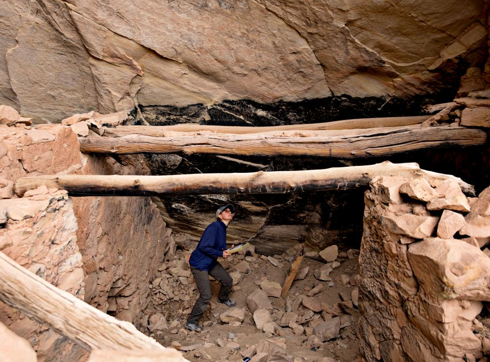 Shanna Diederichs, an architectural conservator, examines a ruin in Bears Ears National Monument and documents its condition,