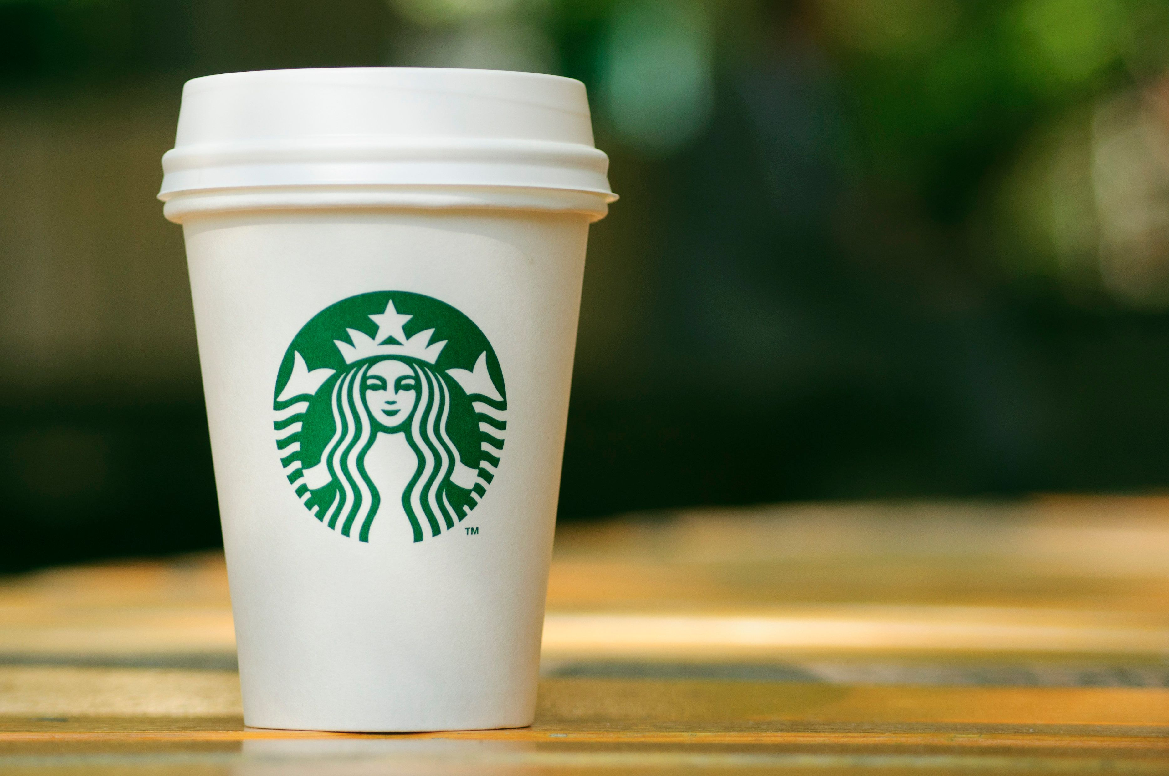 Tall Starbucks to go cup on wooden table