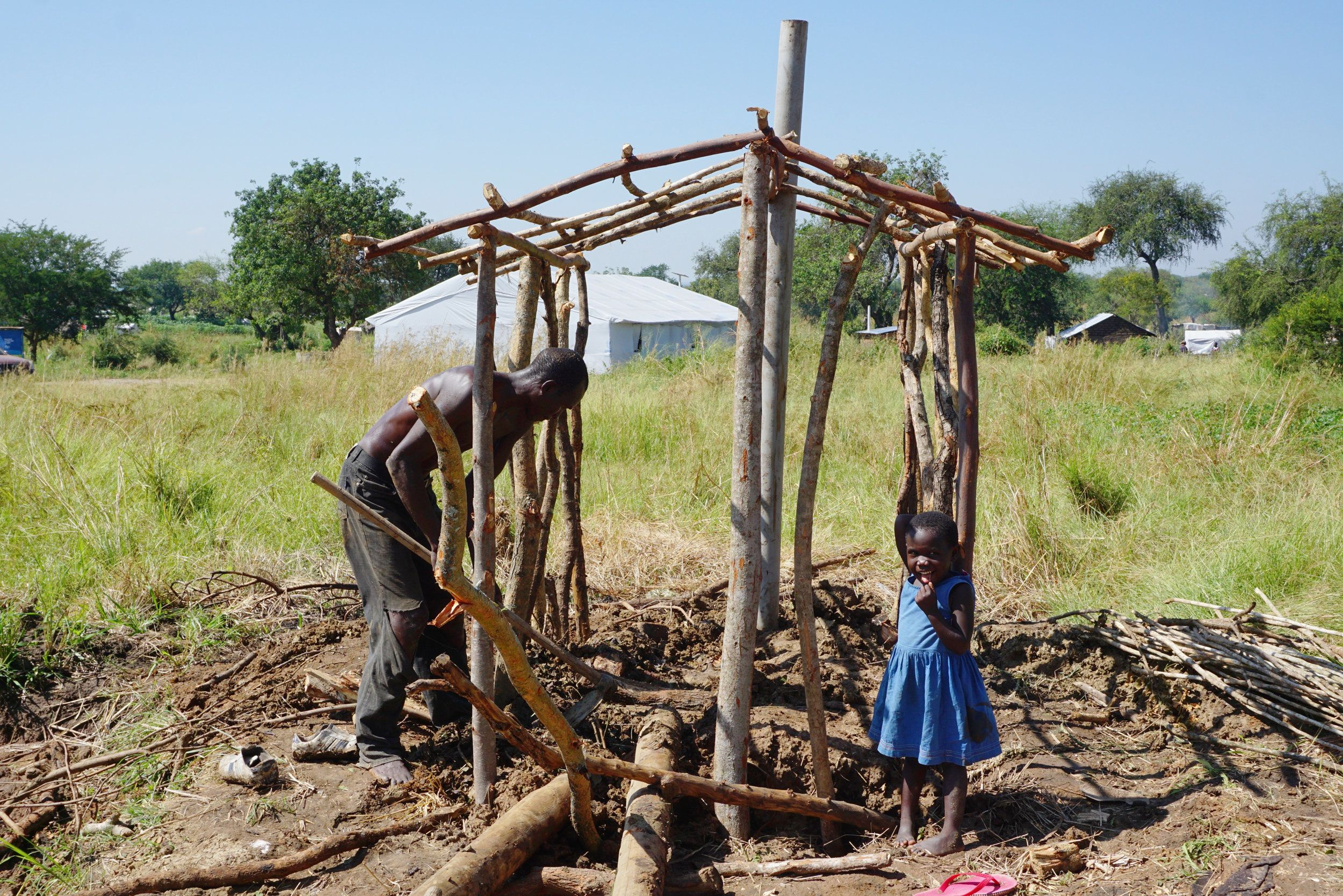 A South Sudanese refugee digs a pit latrine for his family in the Bidi Bidi refugee camp.