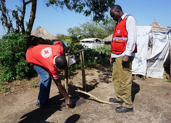 Uganda Red Cross volunteers fix a pedal-operated soap dispenser for hand washing in an effort to reduce infections