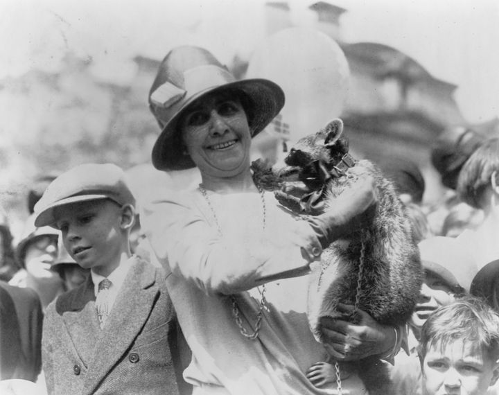 First Lady Grace Coolidge with her pet raccoon at the White House Easter Egg Roll in 1927.