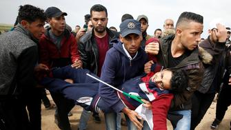 A wounded Palestinian is evacuated during clashes with Israeli troops during a tent city protest along the Israel border with Gaza, demanding the right to return to their homeland, east of Gaza City March 30, 2018. REUTERS/Mohammed Salem