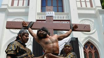 An Indian actors re-enact the crucifixion of Jesus Christ (C) during a Passion play on Good Friday in Bangalore on March 30, 2018.    Passion plays are a dramatic presentation depicting the suffering and death of Jesus Christ and are an integral part of Good Friday celebrations for Catholics. / AFP PHOTO / MANJUNATH KIRAN        (Photo credit should read MANJUNATH KIRAN/AFP/Getty Images)