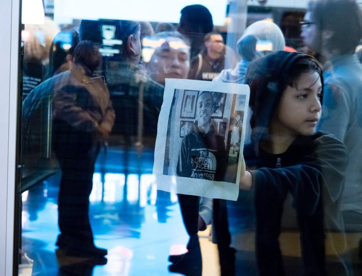 A young demonstrator holds a photo of Stephon Clark to the glass of the doors to Golden 1 Center in Sacramento, California, a