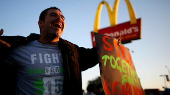 Striking McDonald's worker Abran Escarzaga, 31, protests outside McDonald's in Los Angeles, California, December 5, 2013. Organizers say fast food workers will strike in 100 U.S. cities, and there will be protests in 100 more, to fight for $15 an hour wages and the right to form a union.  REUTERS/Lucy Nicholson (UNITED STATES - Tags: BUSINESS CIVIL UNREST FOOD)