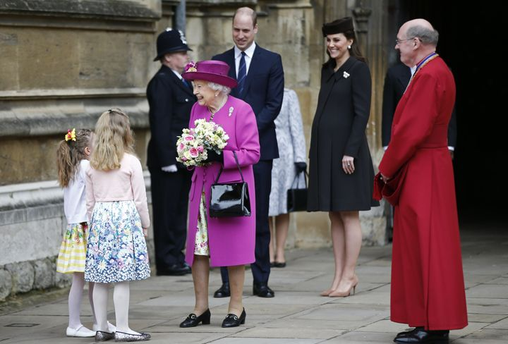 The queen wore a magenta hat and coat over a floral dress.