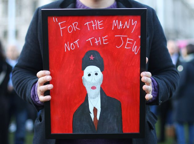 A demonstrator holding a painting during a demo against anti-Semitism in the Labour Party in Westminster.