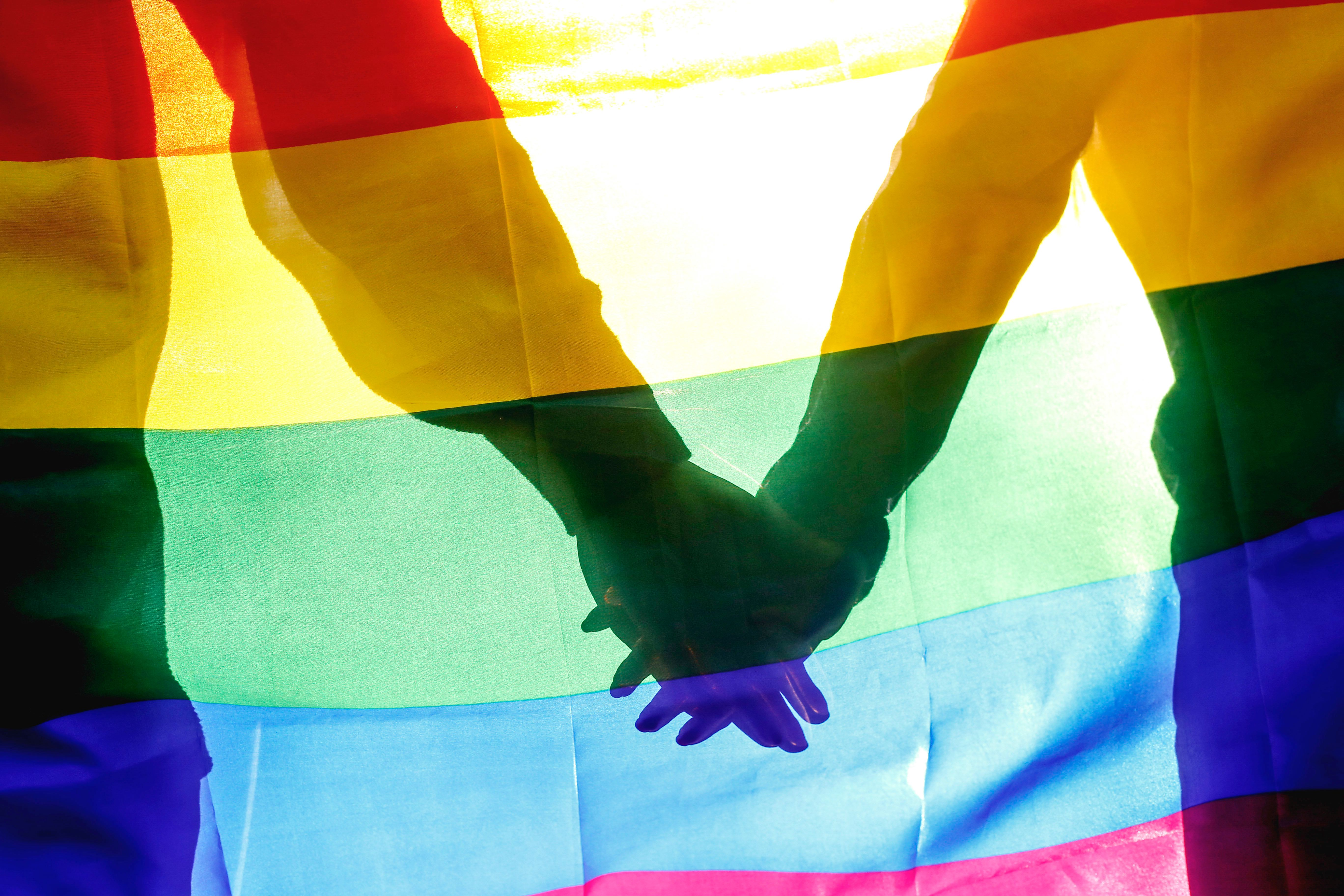 People, homosexuality, same-sex marriage, gay and love concept - close up of happy male gay couple hugging and holding rainbow flag