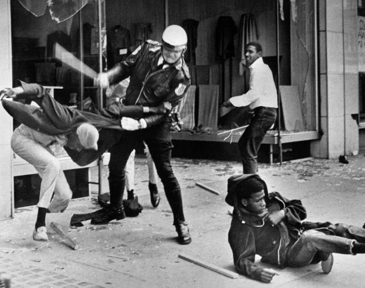 A police officer uses his nightstick on a youth reportedly involved in the looting that followed the breakup of a march led b