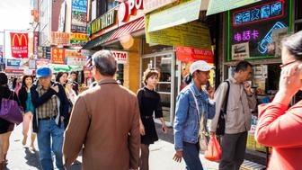 Flushing, NY, USA - September 21, 2015: People walking down a busy street in Flushing Queens' Chinatown. Several people are talking on their cellphones. A Chinese script neon sign is visible in the nearest storefront. Various other businesses visible include Popeye's Chicken, a bakery, tattoo parlor, and McDonald's.