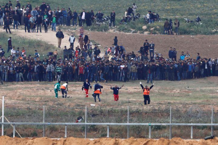 Palestinian paramedics evacuate an injured man on the Gaza side of the Israel-Gaza border on Friday.